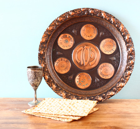 seder: passover background  plate, wine and matzoh  jewish passover bread  over wooden background   Stock Photo