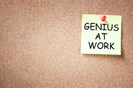open minded: sticky note over cork board with the phrase genius at work  room for text