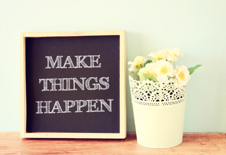 blackboard over wooden shelf with the phrase make things happen   photo