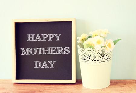 Feliz Día de la Madre s escrito en la pizarra y el ramo de flores sobre fondo de madera