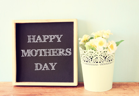 Happy Mother s Day written On Blackboard and bouquet of flowers on wooden background