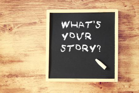 persona escribiendo: mano niño sosteniendo la tiza y escribir lo que es su historia una vista superior de pizarra