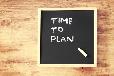 tactic: chalkboard with the phrase time to plan written on it  room for text    Stock Photo