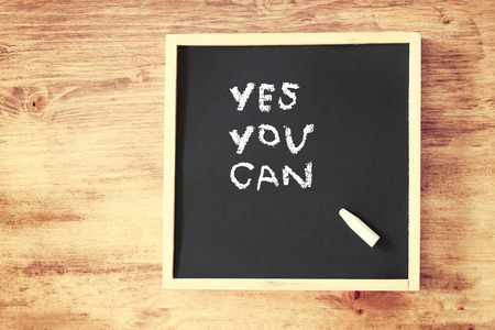 chalkboard with the phrase yes you can written on it  room for text   photo