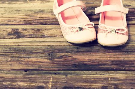 little girl feet: girl shoes over wooden deck floor  filtered image