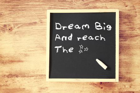 the phrase dream big written on chalkboard photo