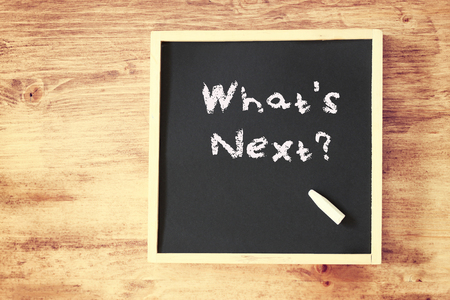 whats next concept written on blackboard over wooden background   photo