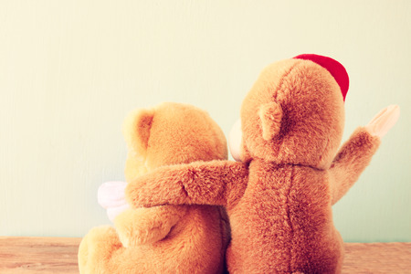arms around: two teddy bears on a shelf with arms around each other  retro vintage filter   Stock Photo