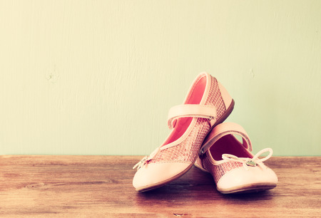 little girl dancing: girl shoes over wooden deck floor  filtered image