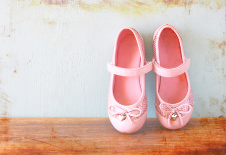 girl shoes over wooden deck floor  filtered image    photo