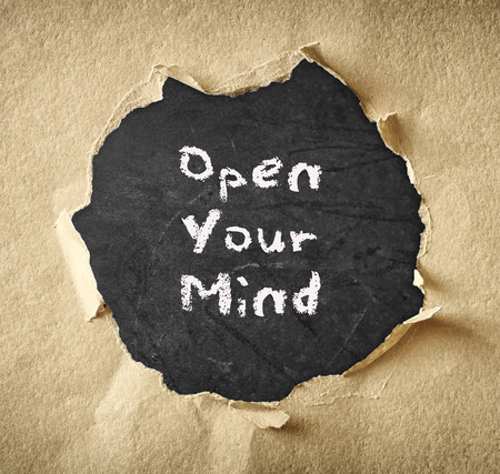 the phrase open your mind written over chalkboard through torn paper   photo