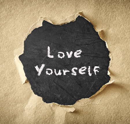self esteem: the phrase love yourself written over chalkboard through torn paper   Stock Photo