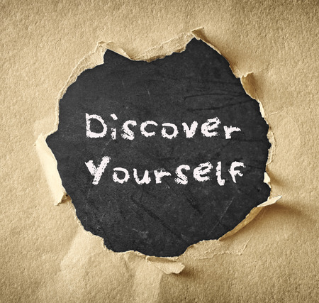 die Phrase Entdecken Sie sich selbst über Tafel durch zerrissene Papier geschrieben Standard-Bild