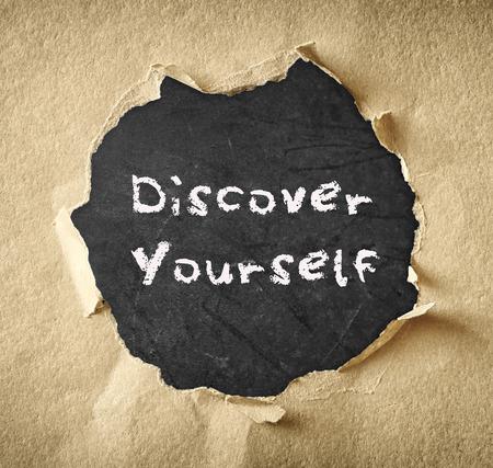 descubrir: la frase descubrirse a uno mismo escrito en la pizarra a trav�s de papel rasgado