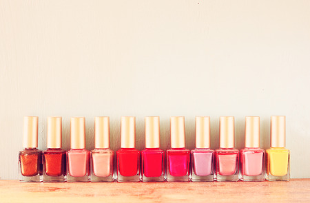 Group of bright nail polishes over wooden board  retro filter  room for text
