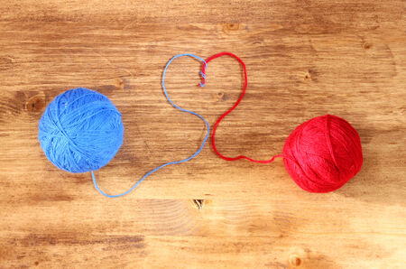 ball of wool: Two wool balls with heart shape over wooden board