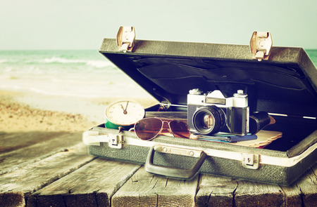 antique suitcase: old case with books and vintage camera on top  travel or adventure concept