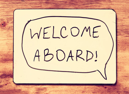 welcome symbol: drawing board with the phrase welcome aboard handwritten over wooden board  filtered image    Stock Photo