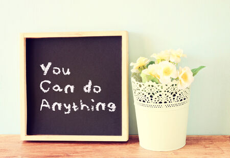 blackboard over wooden shelf with the phrase you can do anything  photo