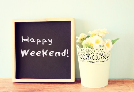 saturday: blackboard over wooden shelf with the phrase happy weekend   Stock Photo