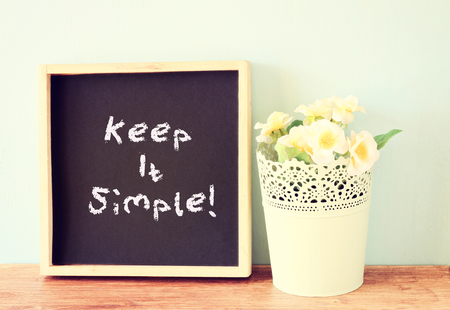 phrase: blackboard with the phrase keep it simple over wooden shelf