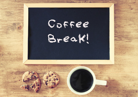 top view of coffee cup cookies and blackboard with the phrase coffee break written on it    photo