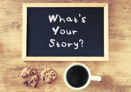 blackboard with the phrase whats your storry and cup of coffee and cookies