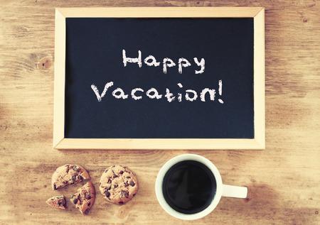 happy life: blackboard and the phrase happy vacation written on it    Stock Photo