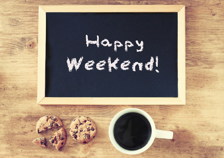 weekend activities: blackboard over wooden table with cup of coffee and cookies and the phrase happy weekend