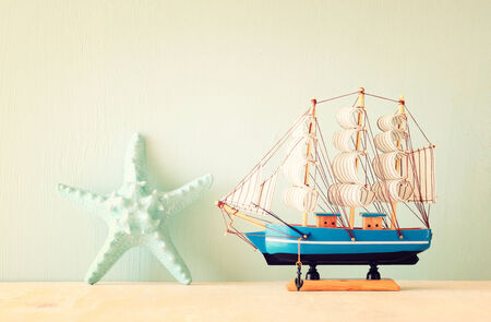 decorative boat and seashell over wooden textured background   photo