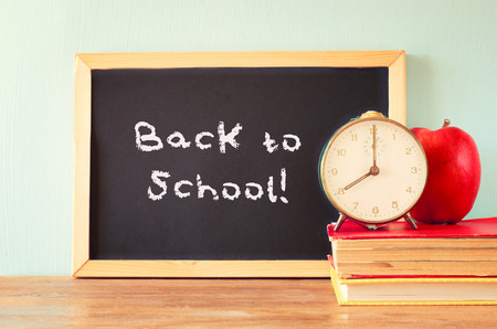 blackboard with the phrase back to school, apple and stack of books  filtered image   photo