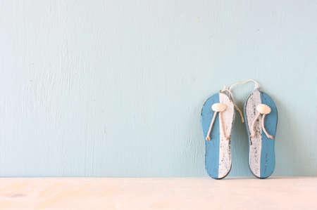 wooden shoes: wooden flip flops over white textured background  summer concept
