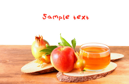 rosh hashanah concept - apple honey and pomegranate over wooden table  isolated    photo