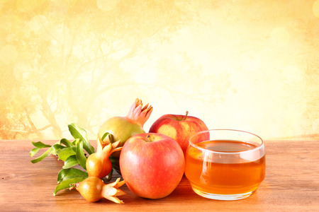 shana tova: rosh hashanah concept - apple honey and pomegranate over wooden table