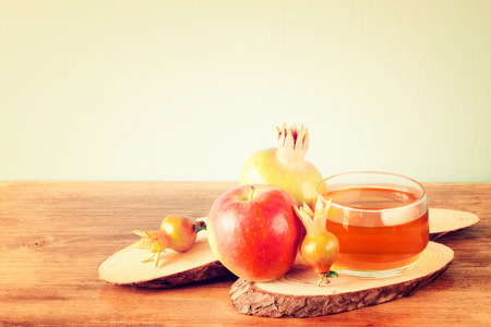 jewish food: rosh hashanah concept - apple honey and pomegranate over wooden table