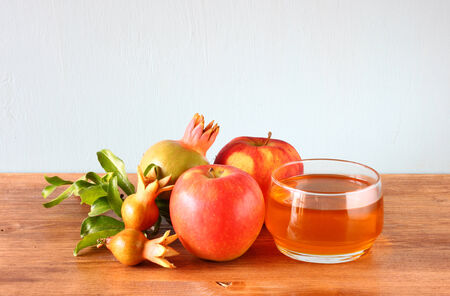 rosh hashanah: rosh hashanah concept - apple honey and pomegranate over wooden table