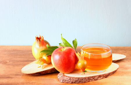 rosh: rosh hashanah concept - apple honey and pomegranate over wooden table
