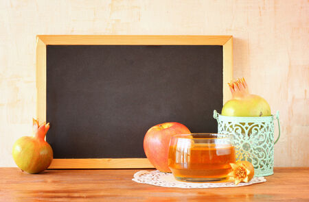 empty blackboard, apple, honey and pomegranate  rosh hshanah concept  photo