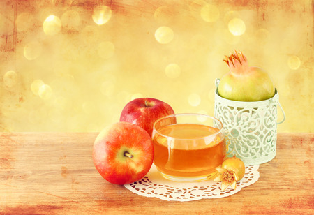 jewish new year: rosh hashanah concept - apple honey and pomegranate over wooden table
