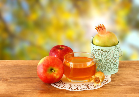 jewish: rosh hashanah concept - apple honey and pomegranate over wooden table