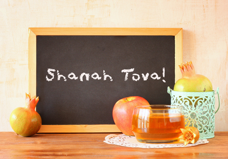 blackboard with the phrase shana tova, apple, honey and pomegranate symbols of rosh hashanah holiday photo