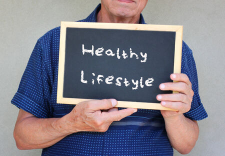 education choice: close up of senior man holding a blackboard with the phrase good health equals good life