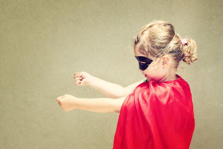 Superhero kid against blue sky background photo