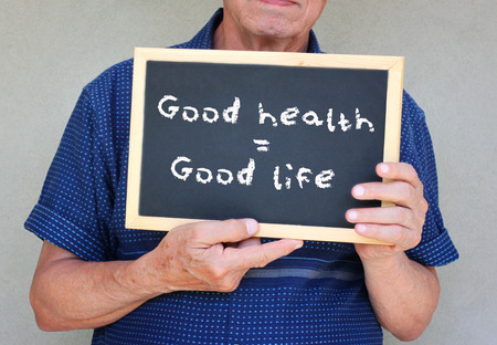 good life: close up of senior man holding a blackboard with the phrase good health equals good life