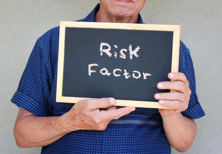 senior man holding blackboard with the phrase risk factor written on it   photo