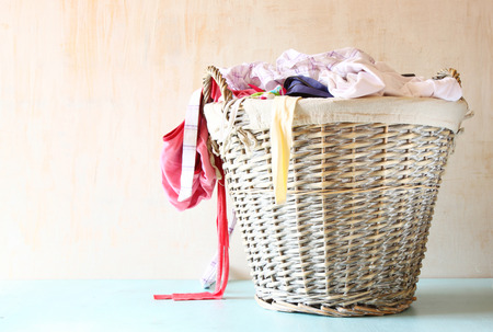 messy clothes: laundry basket full with clothes