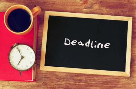 blackboard with the word deadline written on it, clock and coffee cup over wooden board   photo