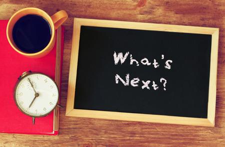 klok, koffie, en blackboad met de zin: wat is volgende op geschreven Stockfoto
