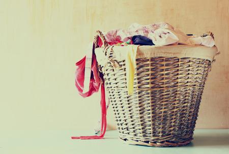 mimbre: cesto de la ropa llena de ropa Foto de archivo