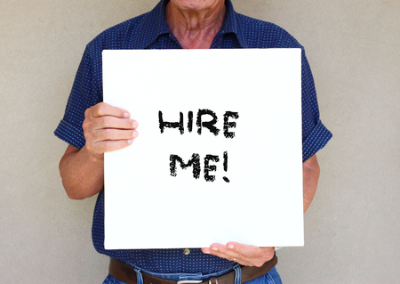 enior man holding white canvas board in front of his face with the phrase hire me   photo